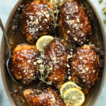 Overhead photo of Balsamic Fig Glazed Chicken garnished with lemon slices and fresh thyme in a round baking dish with a serving spoon resting under one of the chicken thighs and a ramekin of chopped walnuts next to the dish.