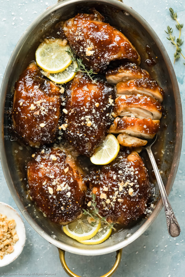 Overhead photo of Balsamic Fig Glazed Chicken in a round baking dish with one of the thighs cut into to showcase the juicy interior of the chicken.