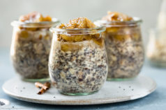 Straight on photo of three individual jars of Banana Overnight Oats on a neutral colored plate with spoons next to the jars and a glass jar of rolled oats blurred in the background.