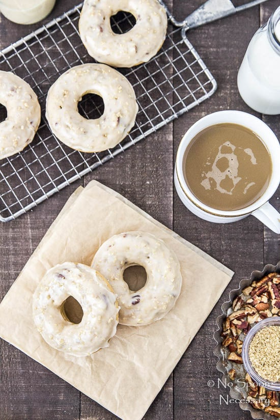 Overhead shot of Brown Sugar & Pecan Baked Cake Donuts with Bourbon Maple Glaze with a cup of coffee, small glass jar of milk and tin filled with pecans surrounding the donuts.