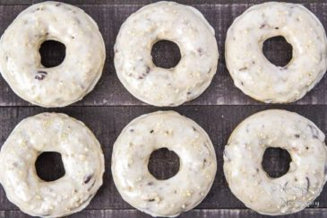 Overhead shot of six Brown Sugar & Pecan Baked Cake Donuts with Bourbon Maple Glaze neatly arranged on a wood board.