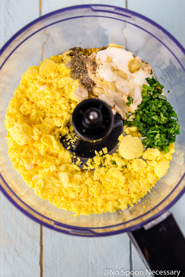 Overhead shot of a food processor bowl filled with the first step of ingredients to make Crab Cake Deviled Egg filling.