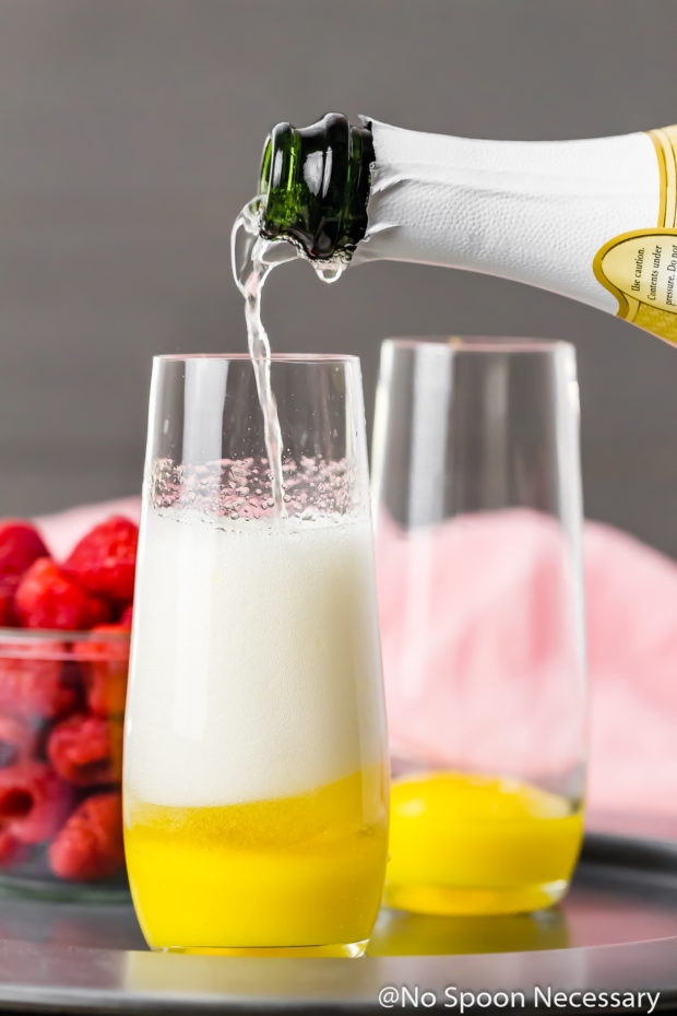 Straight on shot of a stemless wine glass filled with Mango puree and champagne being poured on top - step 2 in how to make Mango Raspberry Mimosa recipe.