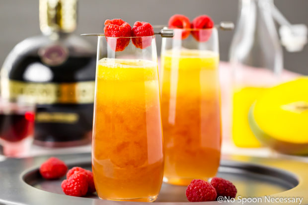 Straight on shot of a Mango & Raspberry Mimosa in a stemless champagne glass on a silver tray with an additional mimosa, bottle of chambord, bottle of mango puree blurred in the background and fresh raspberries scattered around the glasses.