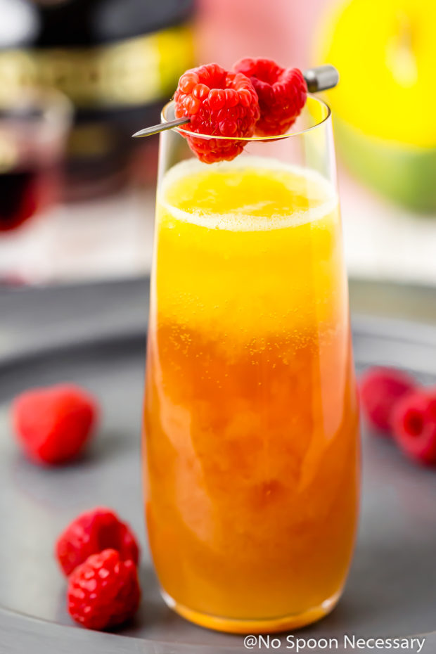 Straight on shot of a Mango & Raspberry Mimosa in a stemless champagne glass on a silver tray with fresh raspberries scattered around the glass.