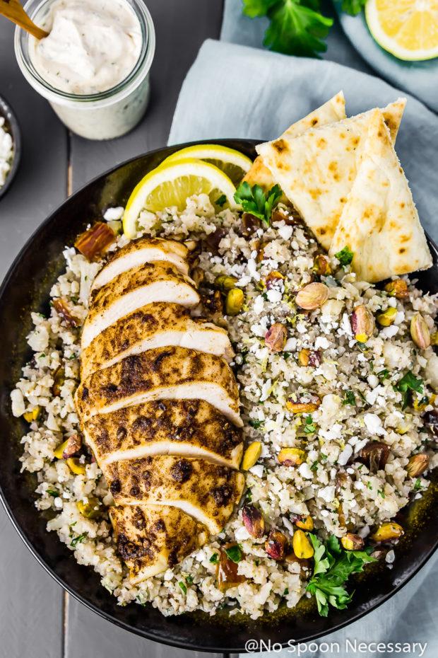 Overhead shot of Moroccan Chicken Couscous Bowls garnished with naan bread and lemon slices with a light blue linen under the bowl and a clear jar of tahini dressing off to the side.