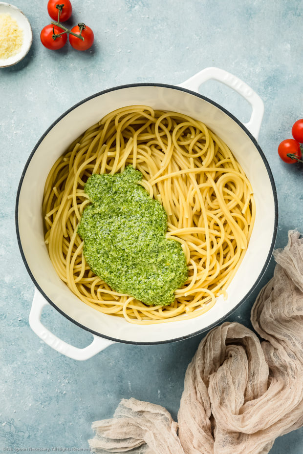 Overhead shot of a large white pot filled with al dente pasta and topped with a generous dollop of homemade arugula pesto - photo of step 4 of the arugula pesto pasta recipe.