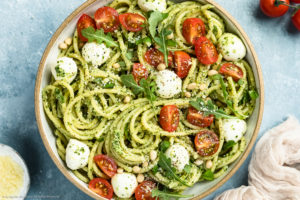 Overhead shot of Arugula Pesto Pasta tossed with mozzarella pearls and halved cherry tomatoes in a white bowl with a ramekin of grated parmesan cheese, a tan linen and vine-ripe cherry tomatoes arranged around the bowl.