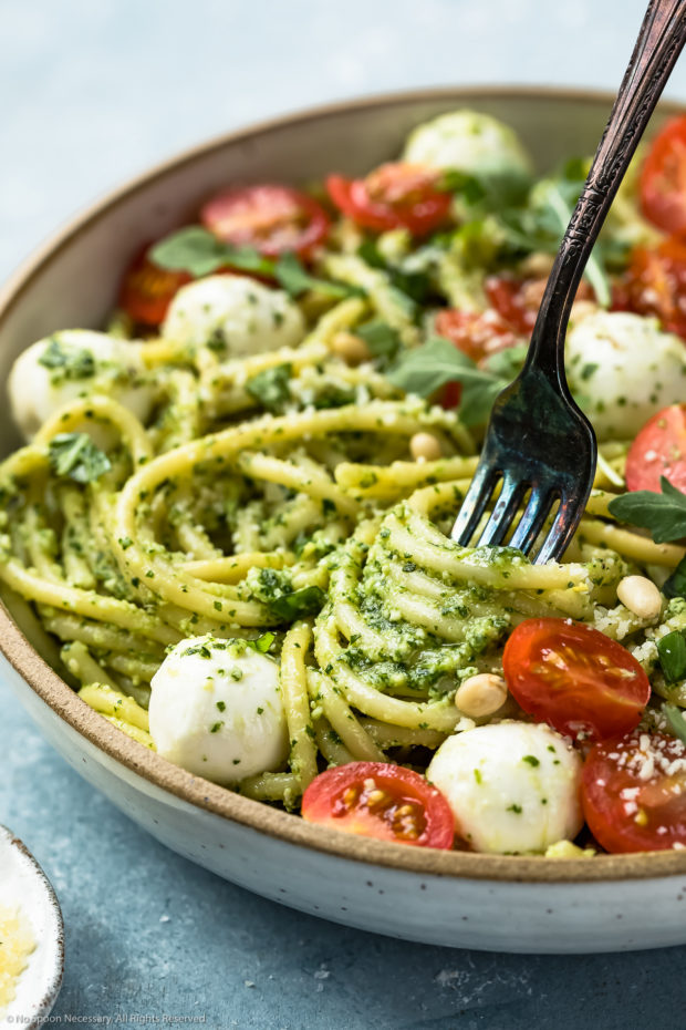 Angled, up-close shot of Arugula Pesto Pasta in a white bowl with a fork inserted and twirled around the pasta to showcase the pesto.