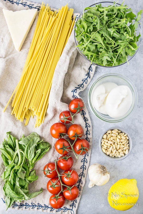 Overhead shot of all the ingredients needed to make Arugula Pesto Pasta with Blistered Tomatoes & Burrata recipe neatly organized on a blueish gray surface with a neutral colored linen.