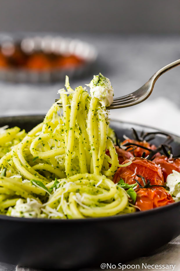 Straight on shot of a black bowl filled with Arugula Pesto Pasta with Blistered Tomatoes and Burrata; with a fork lifting the pasta up and out of the bowl.