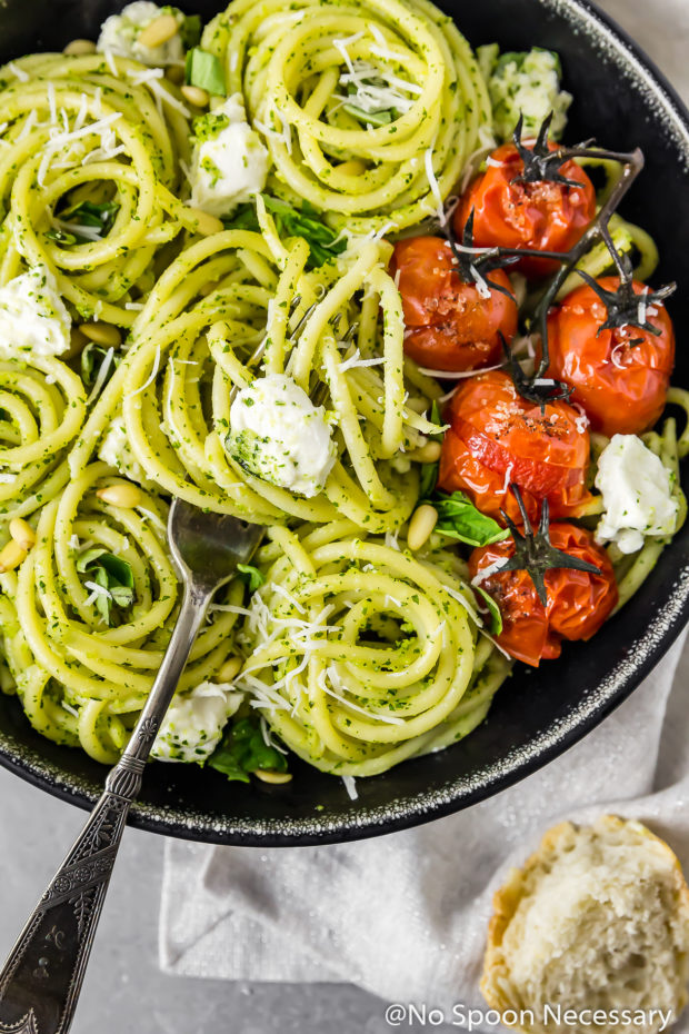 Overhead shot of a black bowl filled with Arugula Pesto Pasta with Blistered Tomatoes and Burrata; with a fork inserted into the bowl of pasta and a torn piece of bread off to the side of the bowl.