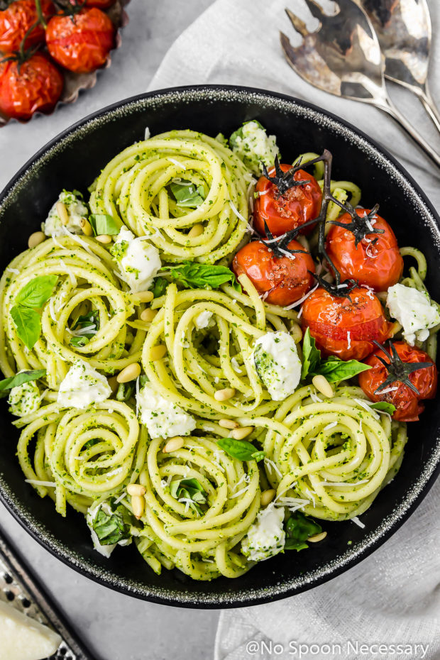 Overhead shot of a black bowl filled with Arugula Pesto Pasta with Blistered Tomatoes and Burrata; with a gray linen under the bowl and serving spoons, more blistered tomatoes and parmesan cheese surrounding the bowl.