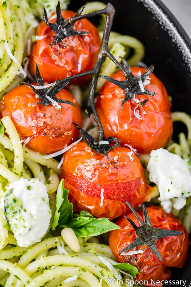 Overhead up close shot of a black bowl filled with Arugula Pesto Pasta with Blistered Tomatoes and Burrata; with the tomatoes being the main focus and mostly filling the frame of the shot.
