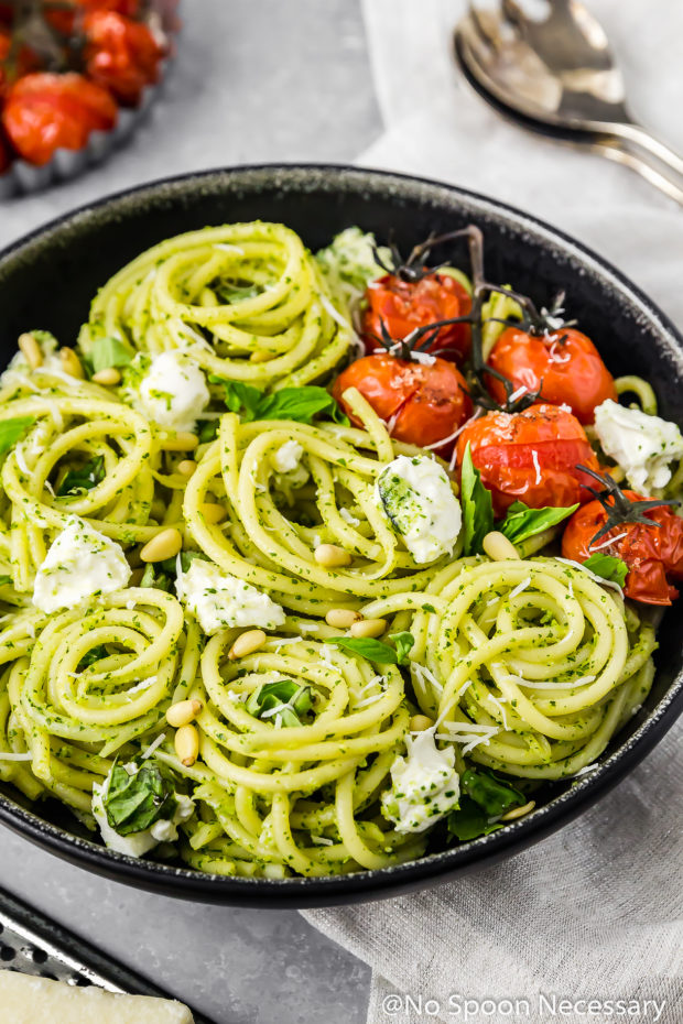 Angled shot of a black bowl filled with Arugula Pesto Pasta with Blistered Tomatoes and Burrata; with a gray linen under the bowl and serving spoons, more blistered tomatoes and parmesan cheese surrounding the bowl.