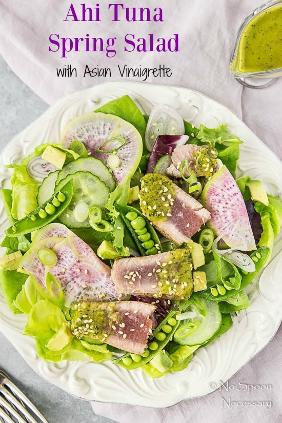 Overhead shot of an Ahi Tuna Spring Salad on a white plate with a pale purple linen under the plate and Asian Vinaigrette in a small glass creamer in the top corner.