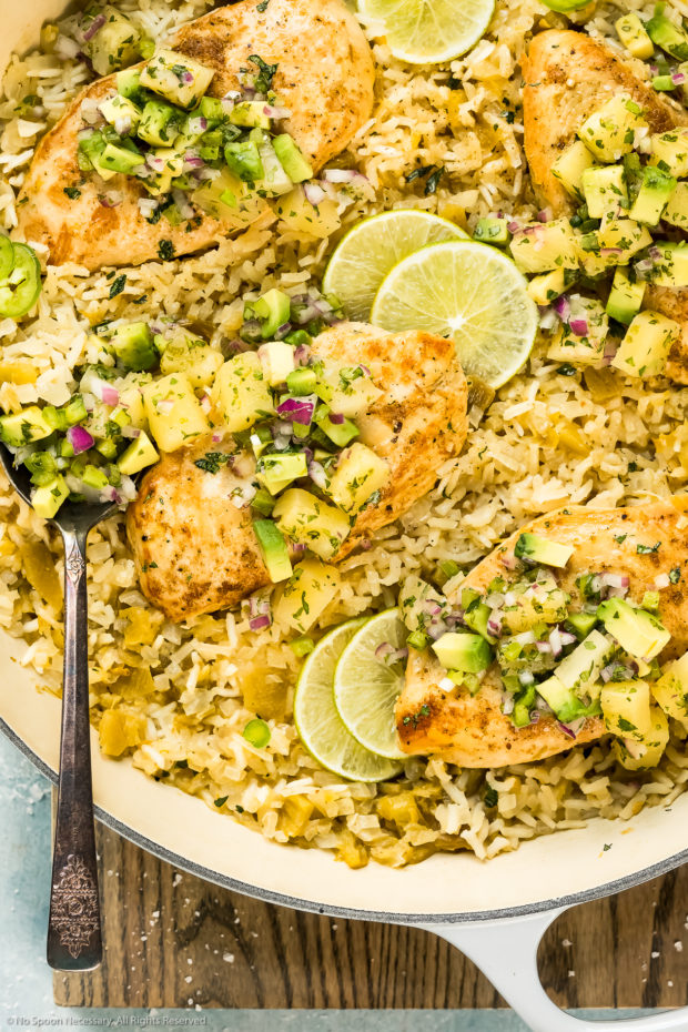 Overhead up close photo of a cooked Cumin Chicken with Rice garnished with slices of limes and pineapple salsa in a large skillet with a serving spoon inserted into the rice.