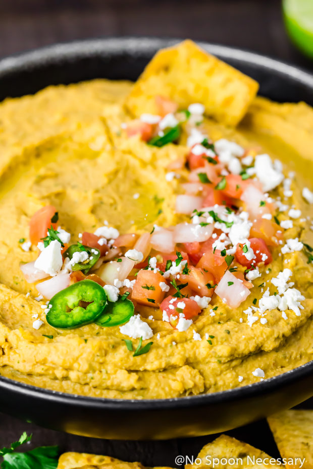 Angled shot of a black bowl filled with Fajita Hummus and topped with pico de gallo, jalapeno slices and cotija cheese with a pita chip dipped into the hummus