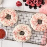 Overhead shot of Raspberry Vanilla Baked Donuts with White Chocolate Glaze on a small wire rack with ramekin of red sprinkles, fresh raspberries, glass jar of milk and a pink linen surrounding the donuts.