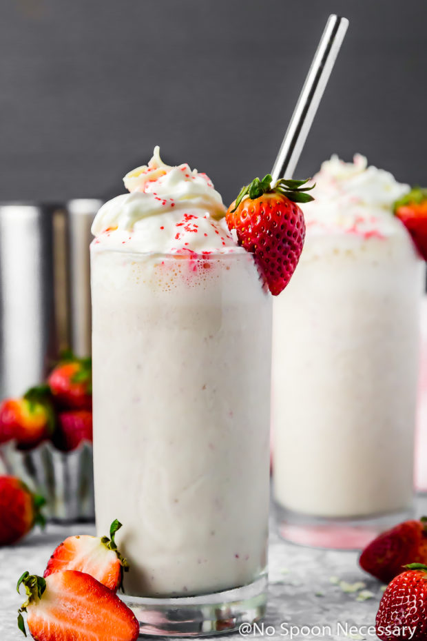Straight on shot of a Strawberry White Chocolate Boozy Milkshake topped with whipped cream and garnished with a fresh strawberry and metal straw; with another milkshake blurred in the background and fresh strawberries strewn all around.