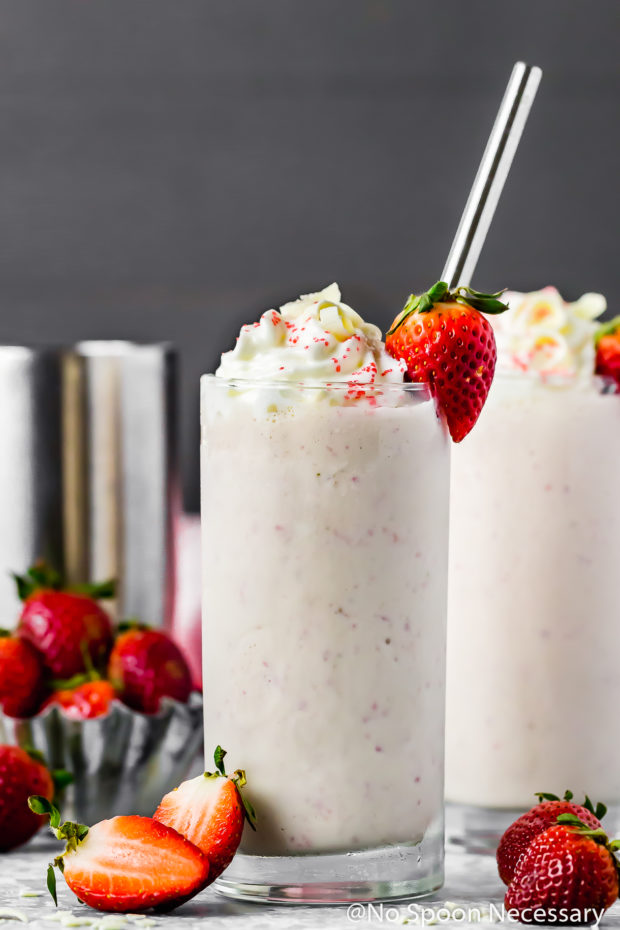 Straight on shot of a Strawberry White Chocolate Boozy Milkshake topped with whipped cream and garnished with a fresh strawberry and metal straw; with another milkshake and cocktail shaker blurred in the background and fresh strawberries strewn all around.