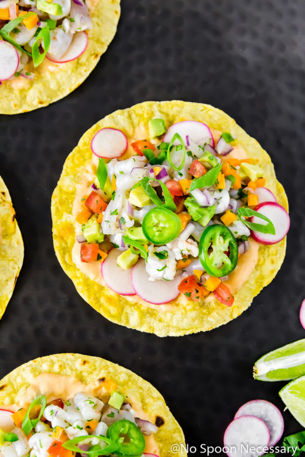 Overhead shot of Baja Shrimp Ceviche Tostadas on a black platter with lime wedges, and sliced radishes.
