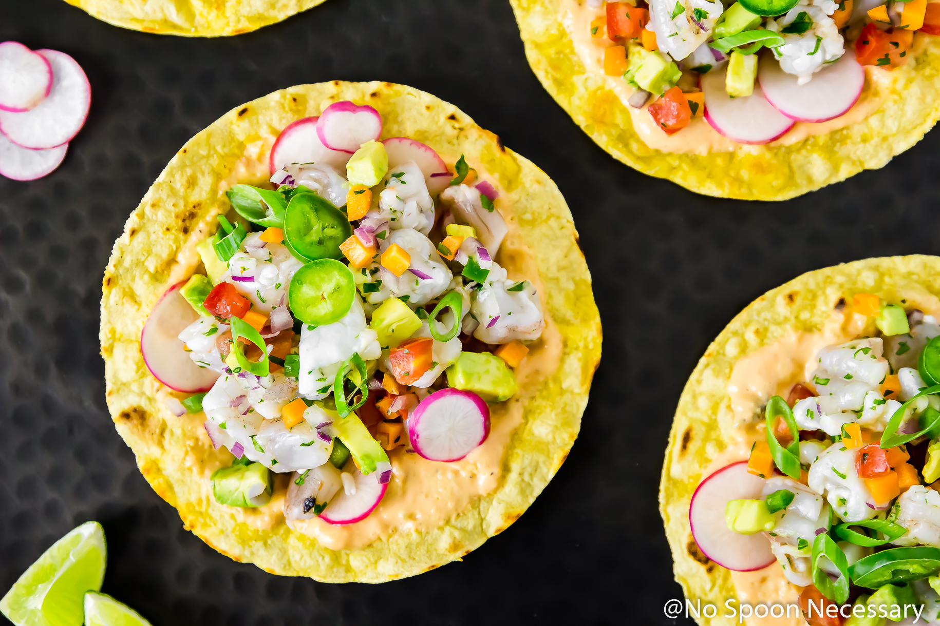 Overhead, landscape photo of Mexican Shrimp Ceviche Tostadas on a black platter with lime wedges, and sliced radishes.
