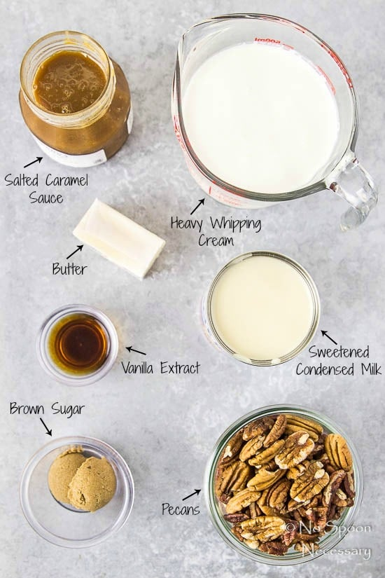 Overhead shot of all the ingredients needed to make No Churn Salted Caramel Ripple Butter Pecan Ice Cream recipe neatly organized on a gray surface with the name of each ingredient written out and pointing to each.