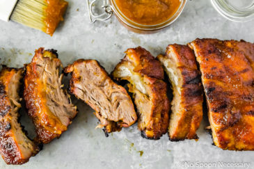 Overhead, landscape shot of a rack of Peach Sriracha BBQ Baby Back Ribs cut apart on a gray surface with a container of BBQ sauce and brush above the rack of ribs.