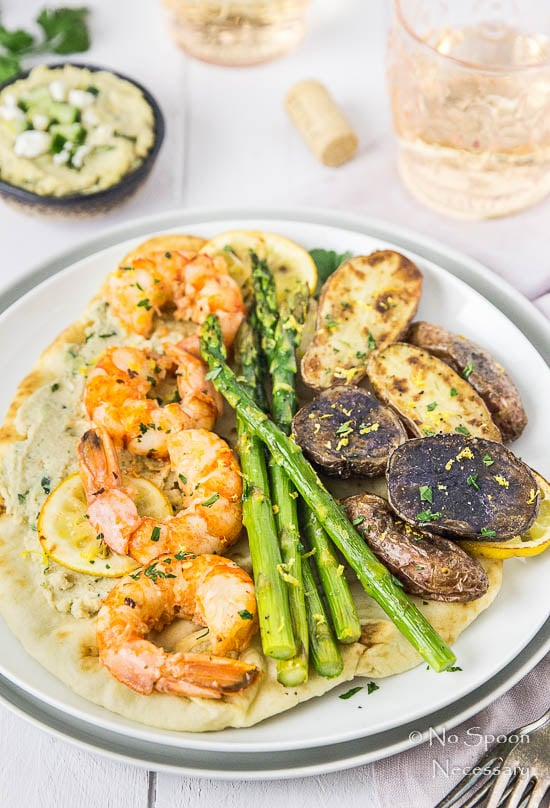 45 degree angle shot of Sheet Pan Garlic & Lemon Shrimp with Asparagus and Fingerling Potatoes served on a piece of naan bread slathered with tzatziki on a white plate, with pink glasses and a ramekin of tzatziki hummus blurred in the background.