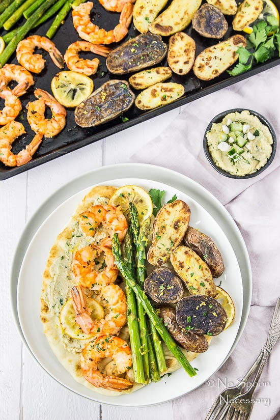 Overhead shot of Sheet Pan Garlic & Lemon Shrimp with Asparagus and Fingerling Potatoes served on a piece of naan bread slathered with tzatziki hummus on a white plate, with the sheet pan meal, purple linen, forks and ramekin of hummus surrounding the plate.