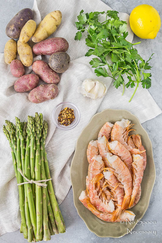 Overhead shot of all the ingredients needed to make Sheet Pan Garlic & Lemon Shrimp with Asparagus and Fingerling Potatoes neatly organized on a gray surface with a neutral colored linen.