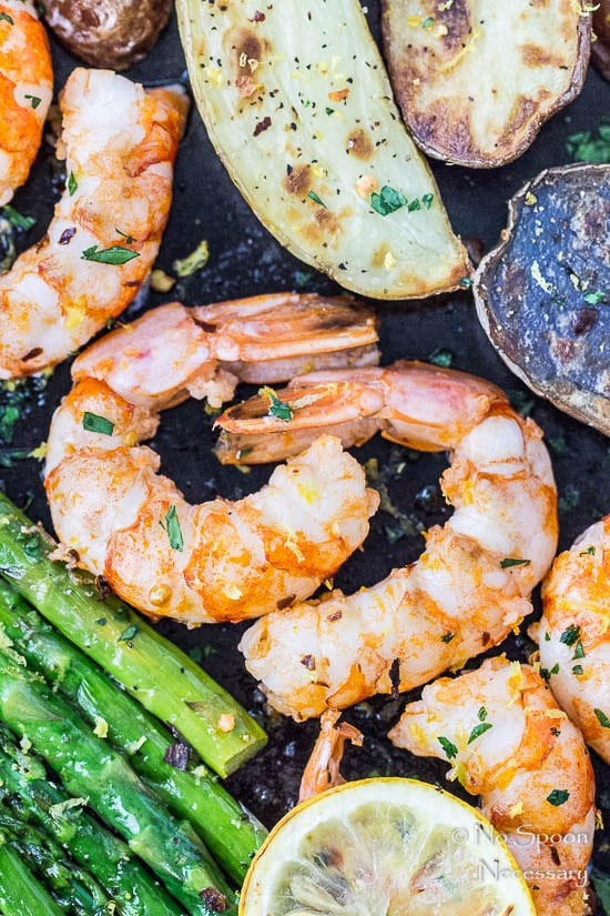 Overhead, up close shot of Sheet Pan Garlic & Lemon Shrimp with Asparagus and Fingerling Potatoes with the focus of the shot on the shrimp.