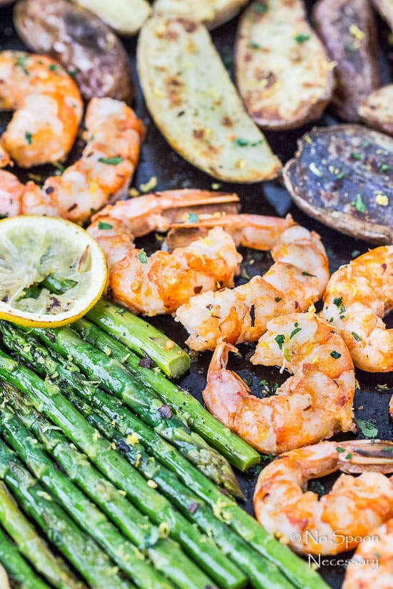 45 degree angle, up close shot of Sheet Pan Garlic & Lemon Shrimp with Asparagus and Fingerling Potatoes garnished with lemon slices.