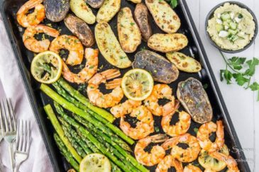 Overhead, landscape shot of Sheet Pan Garlic & Lemon Shrimp with Asparagus and Fingerling Potatoes garnished with lemon slices and parsley with a purple linen, forks, and small ramekin of tzatziki hummus surrounding the pan.
