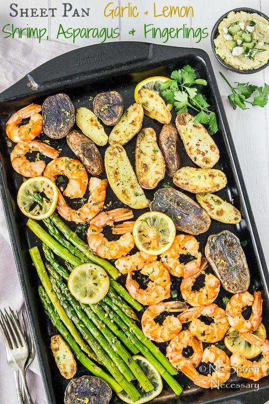 Overhead shot of Sheet Pan Garlic & Lemon Shrimp with Asparagus and Fingerling Potatoes garnished with lemon slices and parsley with a purple linen, forks, and small ramekin of tzatziki hummus surrounding the pan.
