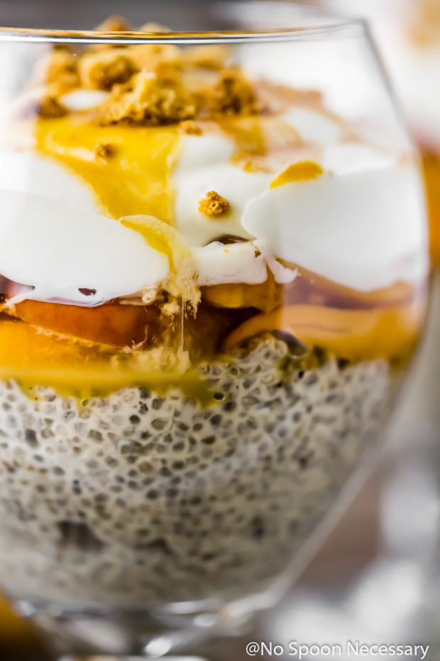Straight on, up-close shot of a Amaretto Peaches & Cream Chia Pudding Trifle in a stemmed glass.