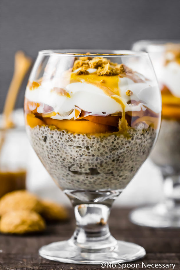 Straight on shot of a Amaretto Peaches & Cream Chia Pudding Trifle in a stemmed glass with amaretti cookies, a jar of caramel sauce and an additional trifle blurred in the background.