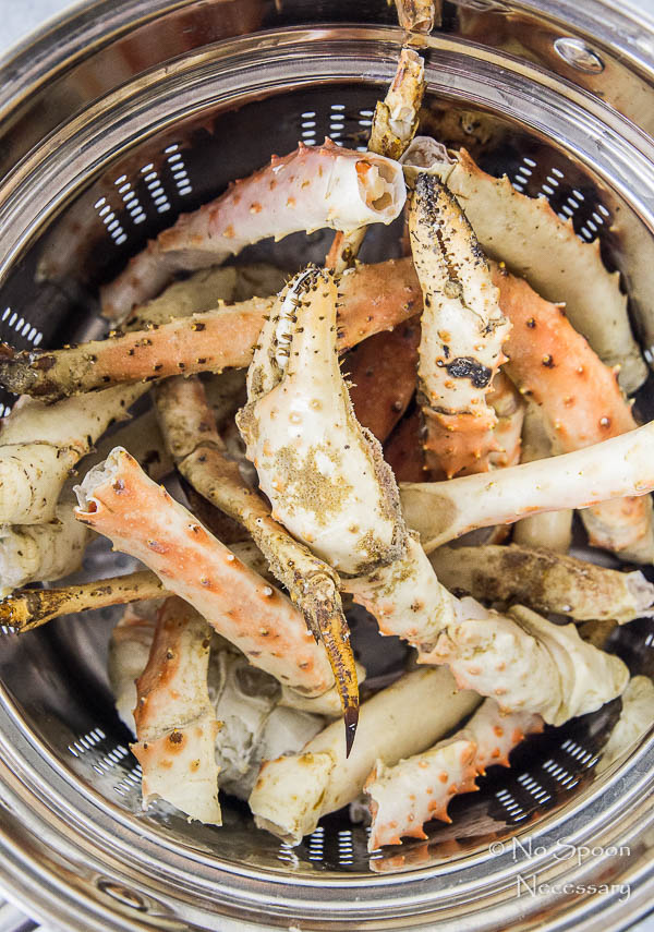 Overhead shot of king crab legs in a steamer basket - step one in the recipe to make Avocado, Mango & Crab Rolls.