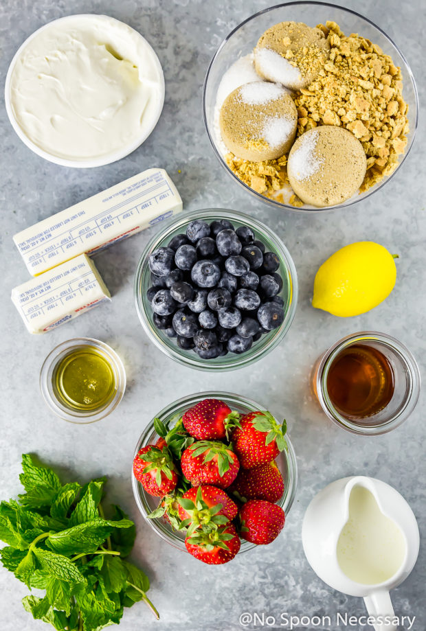 Overhead shot of all the ingredients needed to make a fruit and yogurt parfait neatly organized in bowls on a gray surface.