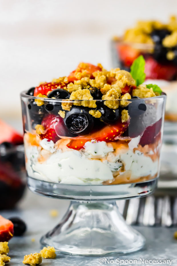Straight on shot of Red White & Blue Boozy Berries Parfait - which consists of layers of mint whipped mascarpone, brandied fruit and graham cracker streusel - in a small parfait glass, with an additional parfait and small bowl of fruit blurred in the background.