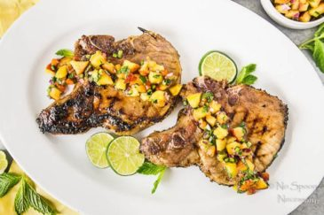 Overhead shot of Ginger Honey Glazed Pork Chops with Peach-Poblano Salsa on a white platter with slices of lime.
