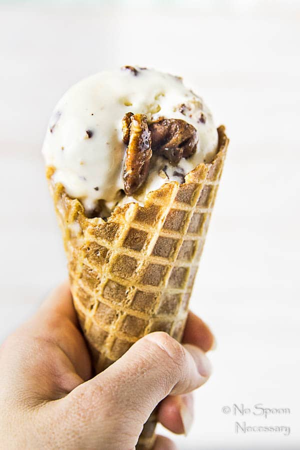Straight on shot of a hand holding a No Churn Salted Caramel Ripple Butter Pecan Ice Cream waffle cone.