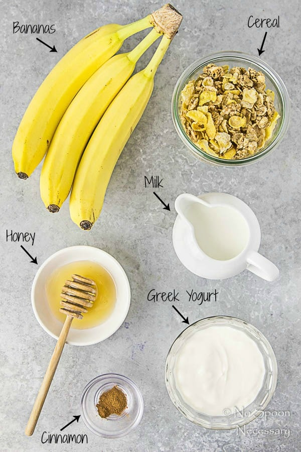 Overhead shot of all the ingredients needed to make Banana & Honey Cereal Breakfast Popsicles recipe neatly organized on a gray surface with the ingredient name written out and pointing to each individual ingredient.