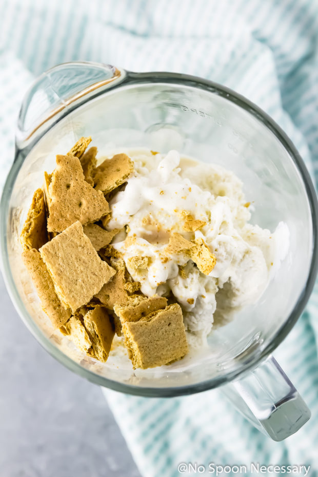 Overhead shot of ice cream and crushed graham crackers in a blender - photo of how to make a lime milkshake.
