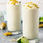 Straight on shot of two Lime Milkshakes topped with whipped cream, crushed graham crackers and lime zest with halved key limes surrounding the glasses and a bottle of tequila in the background.