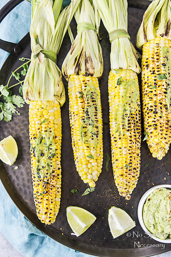 Overhead, up close shot of Grilled Corn with Avocado Sriracha Butter on a black platter with lime wedges and fresh cilantro.