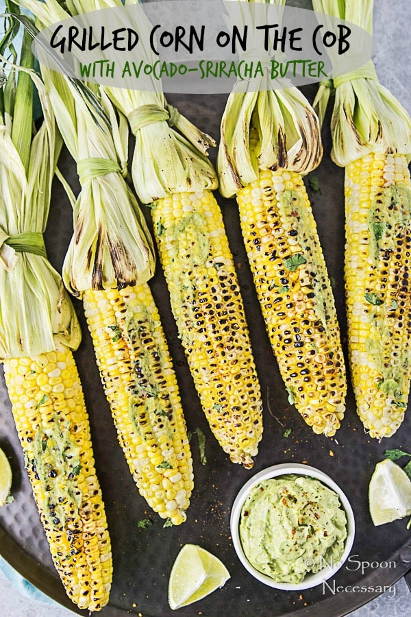 "Overhead shot of Grilled Corn with Avocado Sriracha Butter on a black platter with lime wedges and fresh cilantro; and the words ""Grilled Corn on the Cob with Avocado-Sriracha Butter"" written on the photo."