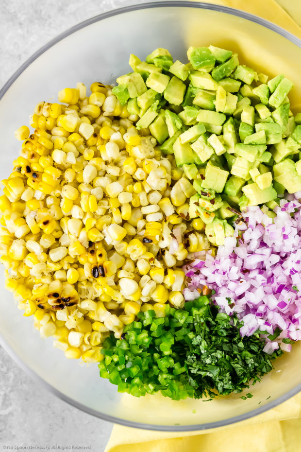 Overhead photo of a glass bowl filled with the ingredients needed to make Avocado & Corn Salsa for scallops.