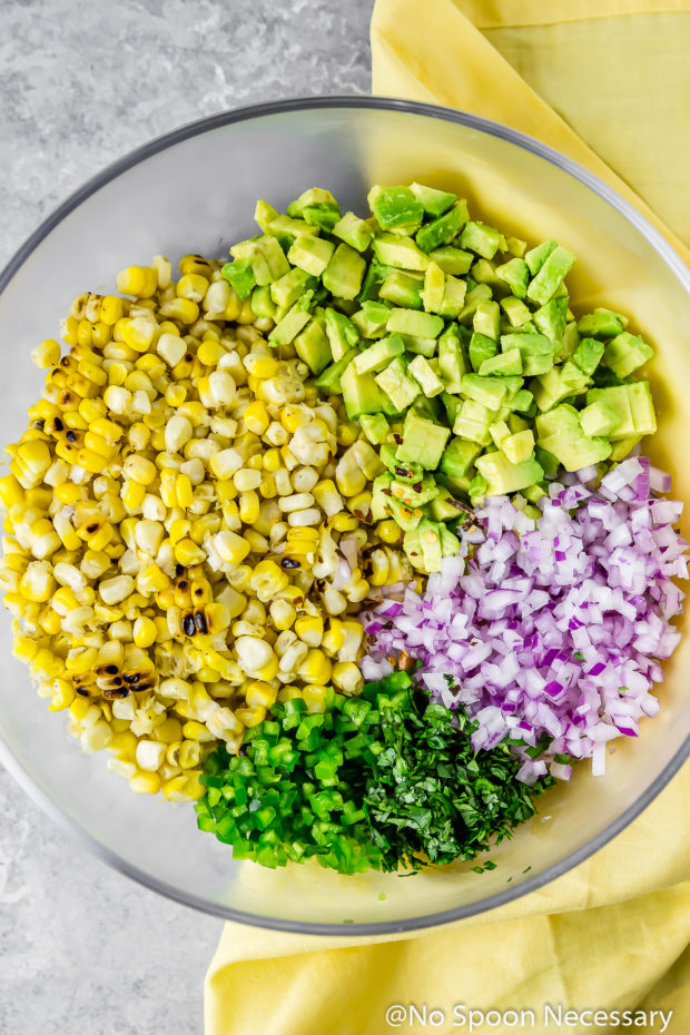 Overhead shot of a glass bowl neatly filled with the ingredients needed to make Avocado & Corn Salsa - one of the main components of Grilled Scallops with Avocado & Corn Salsa recipe.